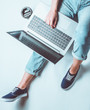 canvas print picture - Freelance concept. Workplace online employee. Fragment of female legs in jeans and sneakers. A woman is sitting on a white background and is using a laptop.
