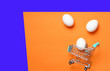 Leinwanddruck Bild - Chicken eggs in mini shopping trolley for shopping on orange blue background, consumer concept, minimalism, top view..