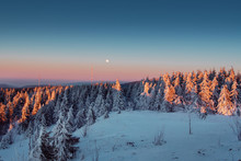 Colorful Sunset Mountain Panorama View In The Winter Season With Snow And Full Moon Rising Over The Mountain Tops With Blue Sky. Harz Mountains National Park In Germany