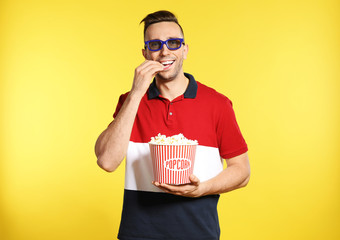 Man with 3D glasses and popcorn during cinema show on color background