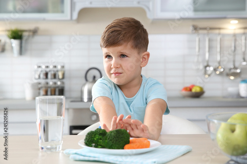 Adorable little boy refusing to eat vegetables at table in kitchen