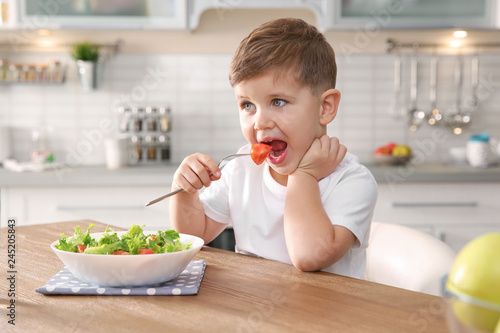Adorable little boy eating vegetable salad at table in kitchen