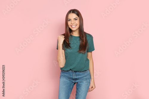 Fotografía  Young woman celebrating victory on color background