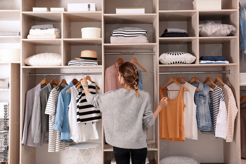 Fototapety, obrazy: Woman choosing outfit from large wardrobe closet with stylish clothes and home stuff