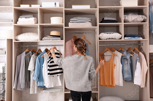 Obraz Woman choosing outfit from large wardrobe closet with stylish clothes and home stuff - fototapety do salonu