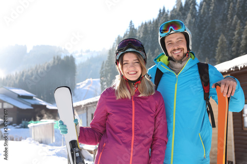 Door stickers Winter sports Happy couple with ski equipment spending winter vacation at mountain resort