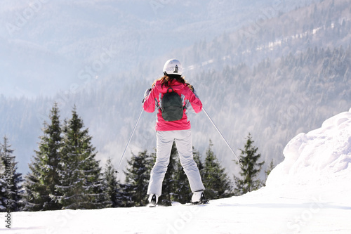Woman skiing on snowy hill in mountains. Winter vacation