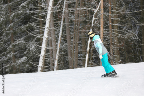 Woman in suit snowboarding on hill, space for text. Winter vacation