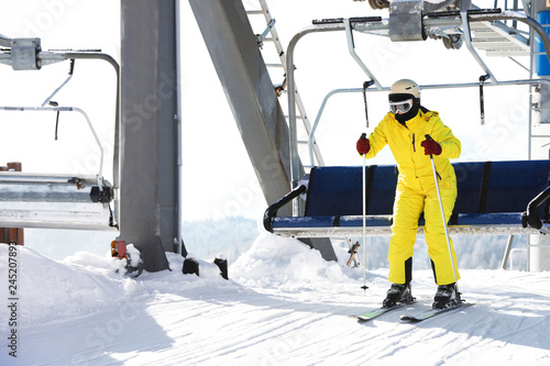 Woman using chairlift at mountain ski resort. Winter vacation