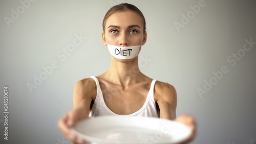 Fotomural Slim girl with taped mouth showing empty plate, severe diet and self-destruction