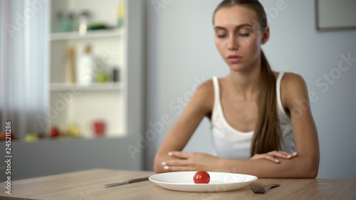 Valokuva  Underweight woman looking at small portion of meal, exhausted body, severe diets