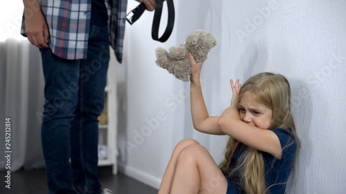 Violence in family, crazy father threatening frightened little girl with belt Wallpaper Mural