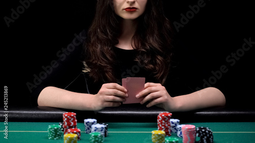 Fotografia Woman player checking her cards combination, bluffing at casino poker game