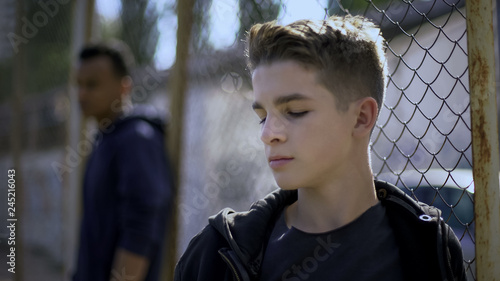 Obraz Teenage boys leaning on metal fence, juvenile detention center, orphanage - fototapety do salonu