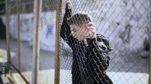 Fotografia, Obraz  Refugee teenager behind fence dreaming about bright future and safety, migration