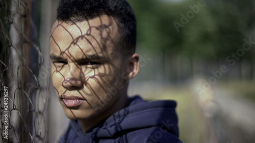 Poor afro-american teenager standing by metal fence, life difficulties concept Canvas Print