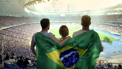 Fotografía  Football fans with Brazilian flag jumping at stadium, cheering for national team