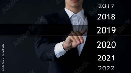 Foto  Businessman selects 2019 year in virtual menu, search for data, business history