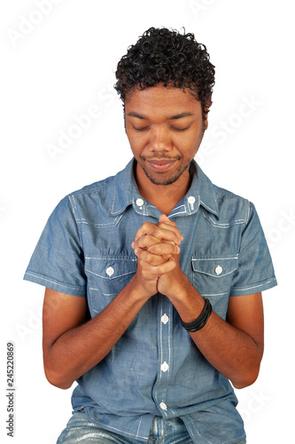 Fotografia  Young Indo-Mauritian or Creole Pastor in training sitting with hands in prayer