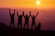 Silhouette group of hikers greetings sun with raised hands against sunset. Hikers walking on a mountain at sunset.