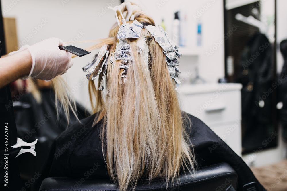 Fototapeta Hairdresser is dying female hair, making hair highlights to his client with a foil.