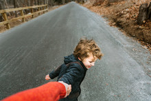 Playful Boy Pulling Brother's Hand On Road