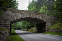 Runners Pass Under Historic Stone Bridge In Acadia National Park