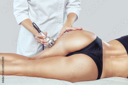 Fotografia, Obraz  The doctor does the Rf lifting procedure on the legs, buttocks, thighs and hips of a woman in a beauty parlor