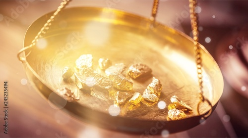 Fototapeta Small gold nuggets in an antique measuring scale
