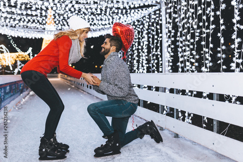 Handsome man proposing a beautiful woman to marry him in ice skating rink.