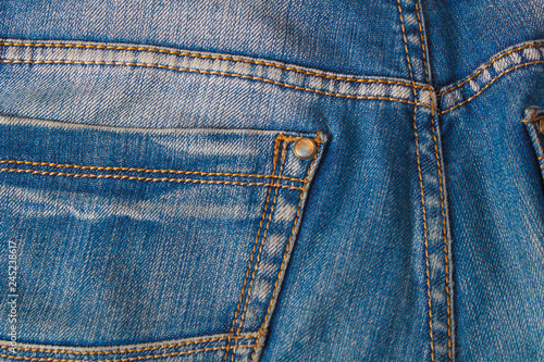 Photographie  Blank real leather jeans label sewed on old worn blue jeans.