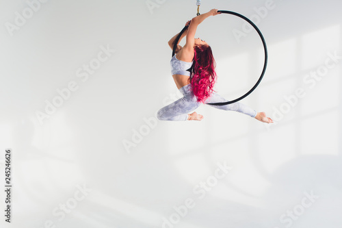 young redhead woman performs acrobatic elements in the air ring on a white background Wallpaper Mural