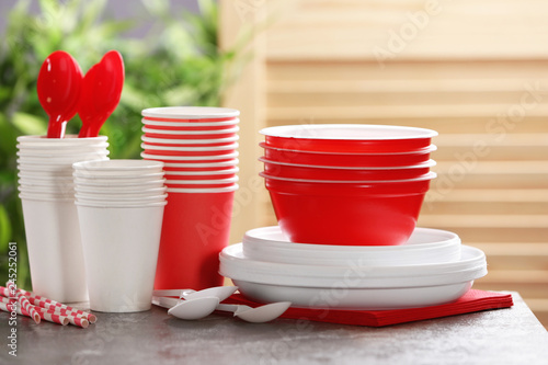 New plastic dishware on table against blurred background. Table setting