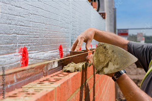 Fotografía  Close up of bricklayer laying brick wall on construction site