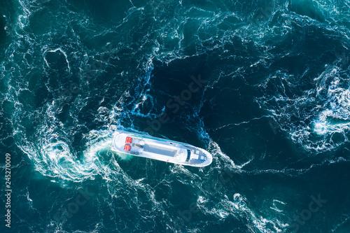荒い海の中を一隻のボートが走っている風景