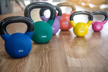 Colorful Kettlebells In A Row On Floor In A Gym, Orange, Violet, Green, Blue,yellow, Pink On Wooden Floor In Gym - Image
