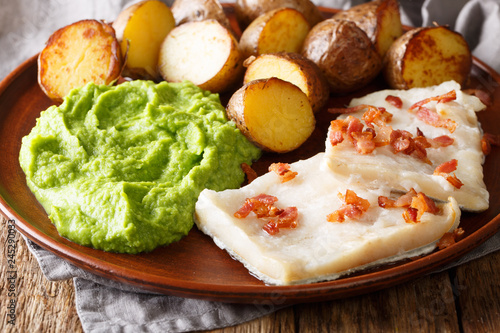Popular Scandinavian food Lutefisk cod with pea puree, baked potatoes and bacon close-up on a plate on the table. horizontal