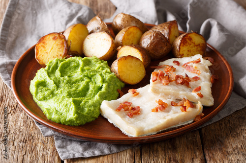 Traditional Scandinavian dish lutefisk served with pea puree, potatoes and bacon close-up. horizontal