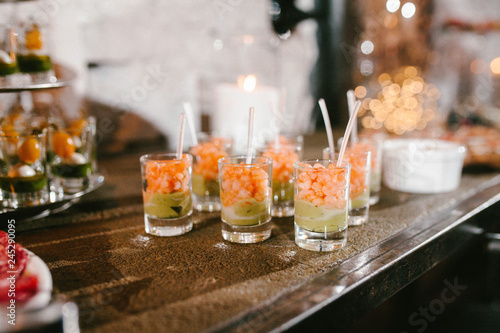Photo appetizer with shrimp and avocado in a glass, buffet table