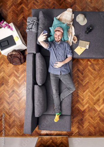 One Young Smiling Man Talking Selfie With His Smart Phone Laying