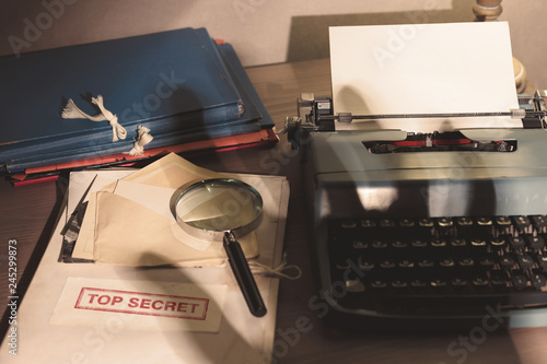 Fotografía  Investigator desk with confidential top secret documents, magnifying glass and typewriter