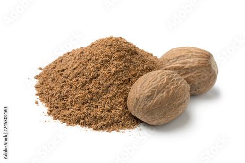 Fototapeta Heap of ground nutmeg and whole nutmeg seeds