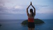 Woman practicing yoga fitness exercise on high place with amazing view of island before sunrise.