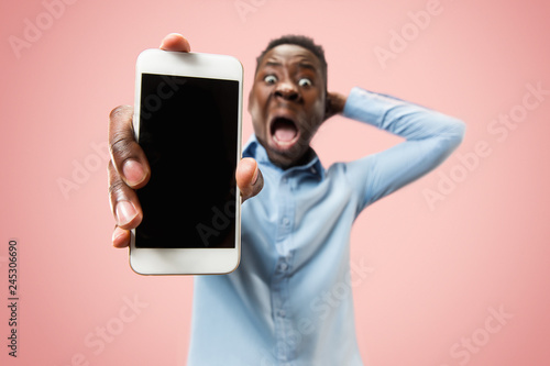 Fotografía  Indoor portrait of attractive young black african man isolated on pink background, holding blank smartphone, smiling at camera, showing screen, feeling happy and surprised
