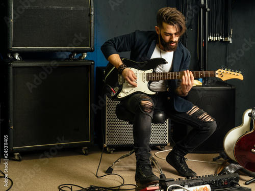Fototapeta Handsome man playing an electric guitar in a studio