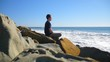 A handsome man practicing meditation and mindfulness on the beach with waves breaking on the shore SLOW MOTION.