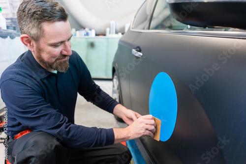 Fototapeta Mann bringt einen Aufkleber mit dem Firmenslogan auf einem Auto an  obraz
