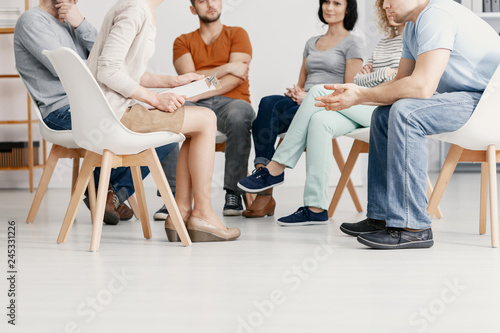 Fotografia  Close-up on people sitting in a circle during group therapy with psychotherapist