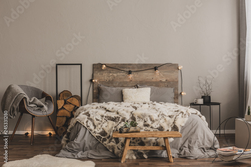Fotografiet  Stylish grey chair with blanket and log of wood next to warm double bed with woo