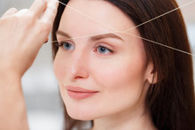 Cosmetologist Plucks Client Eyebrows By Thread. Close Up